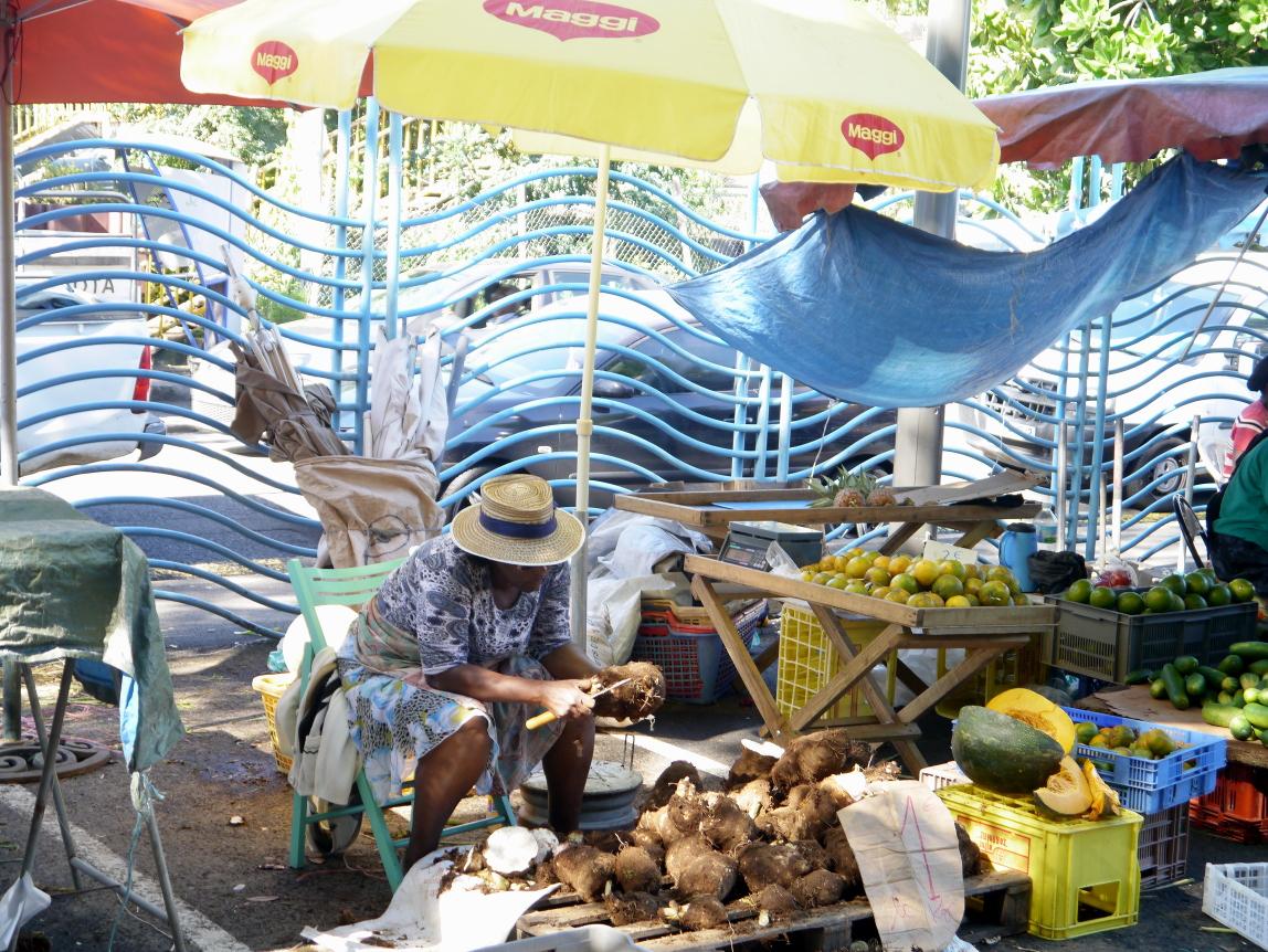 Une marchande soigne la présentation de ses «dachines» et de ses «giraumons»