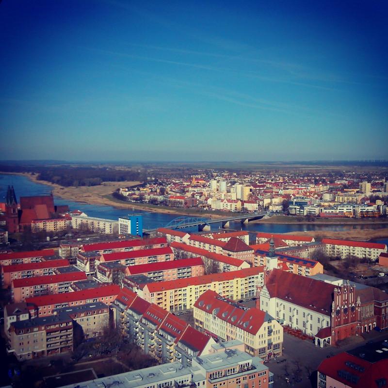 Vue de Frankfurt depuis l'«Oderturm» (la Tour de l'Oder), le plus haut édifice de la ville, en mars 2014. L'immeuble blanc et rouge en bas à droite est la mairie, devant laquelle j'ai photographié Silvia et Uwe. Le fleuve, l'Oder, sépare l'Allemagne de la Pologne. Sur l'autre rive, on distingue la ville polonaise de Słubice. Quelque part au milieu de ces immeubles, Nicole se terre...